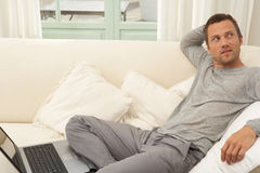 Young attractive man on couch with laptop at home. Royalty Free Stock Photos