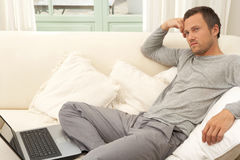 Young attractive man on couch with laptop at home. Stock Photos