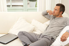 Young attractive man on couch with laptop at home. Royalty Free Stock Photo
