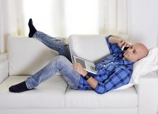 Young attractive man couching with computer and cellphone. Young latin man lying on couch working on computer and talking on mobile phone Royalty Free Stock Photography