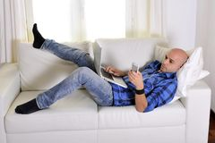 Young attractive man couching with computer and phone. Young latin man lying on couch working on computer and texting on mobile phone Stock Photography