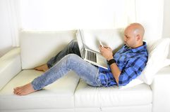 Young attractive man couching with computer and phone. Young latin man lying on couch working on computer and texting on mobile phone Royalty Free Stock Photo