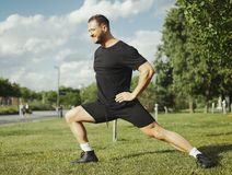 Young attractive man doing lunge outdoor in the park. Side view. stock photos