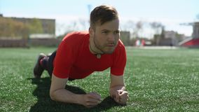 Plank on a stadium lawn. Young attractive man is doing plank exercise on a stadium lawn stock footage