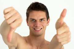Young attractive man doing thumb up. And other thumb down Royalty Free Stock Images
