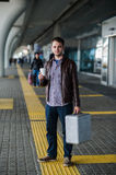 Young attractive man drinking coffee on his way near the airport terminal looking to the camera royalty free stock image