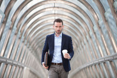 Young attractive man drinking coffee on his way Stock Photography