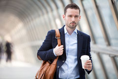 Young attractive man drinking coffee on his way Royalty Free Stock Image
