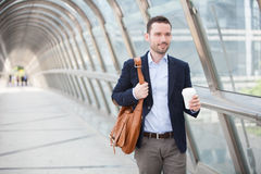 Young attractive man drinking coffee on his way Royalty Free Stock Images
