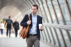 Young attractive man drinking coffee on his way Stock Images