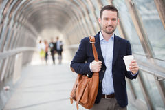 Young attractive man drinking coffee on his way Royalty Free Stock Photos