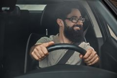 A modern bearded man driving a car Royalty Free Stock Images