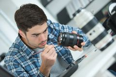 Young attractive man fixing dslr camera lense. Male Royalty Free Stock Photos
