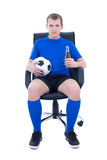 Young attractive man in football form sitting with ball and bott Stock Image