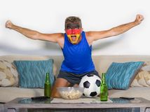 Young attractive man football supporter with Germany flag painted face happy and excited watching cup match on TV celebrating vict. Ory goal crazy with beer and Royalty Free Stock Photo