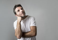 Young attractive man gesturing thoughtful as if daydreaming for Stock Photography