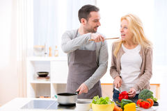 Young attractive man give food to his wife to taste Royalty Free Stock Images