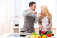 Young attractive man give food to his wife to taste Royalty Free Stock Photos