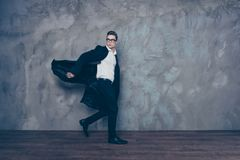 Young attractive man in glasses and black coat is rushing somewh Royalty Free Stock Photography