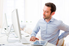Young attractive man got a back pain at the office Royalty Free Stock Photography