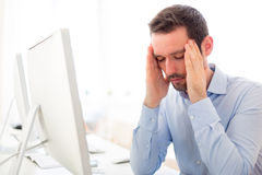 Young attractive man got a headache at the office Stock Images