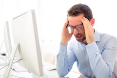 Young attractive man got a headache at the office Royalty Free Stock Images