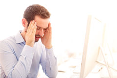 Young attractive man got a headache at the office Royalty Free Stock Photos