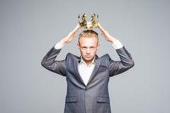Young attractive man in a gray suit holding above his head a golden crown on a gray background. Young attractive man in a blue suit holding above his head a royalty free stock images