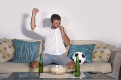 Young attractive man happy and excited watching football match on TV celebrating victory goal crazy kissing team shirld jersey in Royalty Free Stock Photography