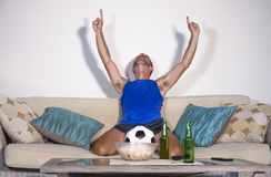 Young attractive man happy and excited watching football match on TV celebrating victory goal crazy and spastic with beer popcorn Royalty Free Stock Photo