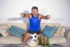 Young attractive man happy and excited watching football match on TV celebrating victory goal crazy and spastic with beer popcorn Royalty Free Stock Photography