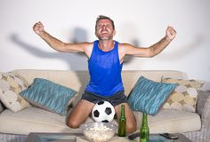 Young attractive man happy and excited watching football match on TV celebrating victory goal crazy and spastic with beer popcorn Royalty Free Stock Image