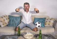 Young attractive man happy and excited watching football match on TV celebrating victory goal crazy and spastic with beer popcorn Stock Photography