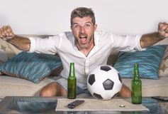 Young attractive man happy and excited watching football match on TV celebrating victory goal crazy and spastic with beer popcorn Royalty Free Stock Photos