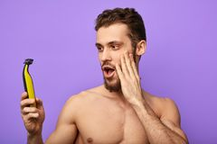 Young attractive man is happy to have positive effect during shaving royalty free stock images