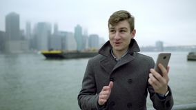 Young man having a video chat near Hudson river with view of Manhattan and showing someone a ferry floating by river. Young attractive man having a video chat stock video