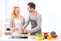 Young attractive man helping out his wife while cooking Stock Photos
