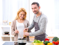 Young attractive man helping out his wife while cooking Stock Images