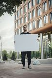 Young attractive man holding blank canvas and looking at the viewer. Front view. stock image