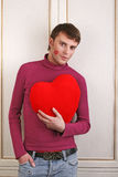 Young attractive man holding a red heart. Looking at camera isolated on white Royalty Free Stock Photography