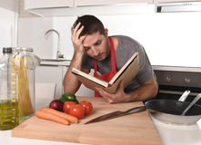 Young attractive man at home kitchen reading recipe book in stress Royalty Free Stock Images