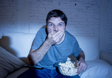 Young attractive man at home lying on couch at living room watching tv eating crudely popcorn holding bowl. And looking mesmerized with blue eyes wide open in Royalty Free Stock Images