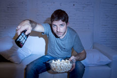 Young attractive man at home lying on couch at living room watching tv holding remote control Royalty Free Stock Images