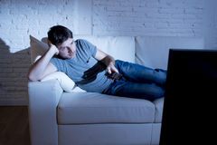 Young attractive man at home lying on couch at living room watching tv holding remote control Stock Image