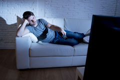 Young attractive man at home lying on couch at living room watching tv holding remote control Stock Photos