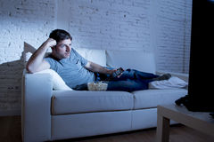 Young attractive man at home lying on couch at living room watching tv holding remote control Royalty Free Stock Photography