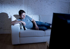 Young attractive man at home lying on couch at living room watching tv holding remote control Stock Photo