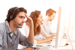 Young attractive man ill-at-ease at work Royalty Free Stock Photo