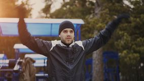 Young attractive man jogger warming up before running outdoors in winter park Stock Images