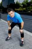 Young attractive man leaning exhausted after running session sweating taking a break to recover in urban street Stock Photo